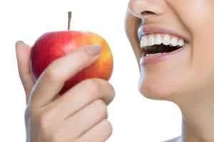A woman with bright white teeth smiling while holding a red apple in front of her mouth