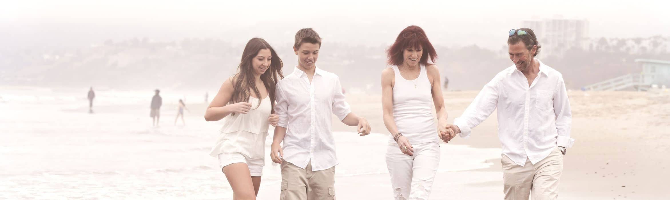 Two parents and two teenagers in white clothes walking happily on the beach in Los Angeles