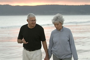 An older couple walking and talking on the beach