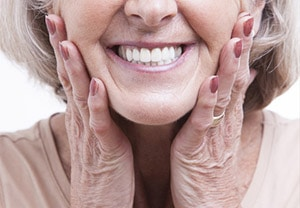 An elderly woman smiling, showing her bright white dentures with her hands on her cheeks