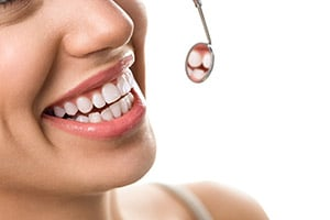 A woman with straight, white teeth smiling and looking into a dental mouth mirror
