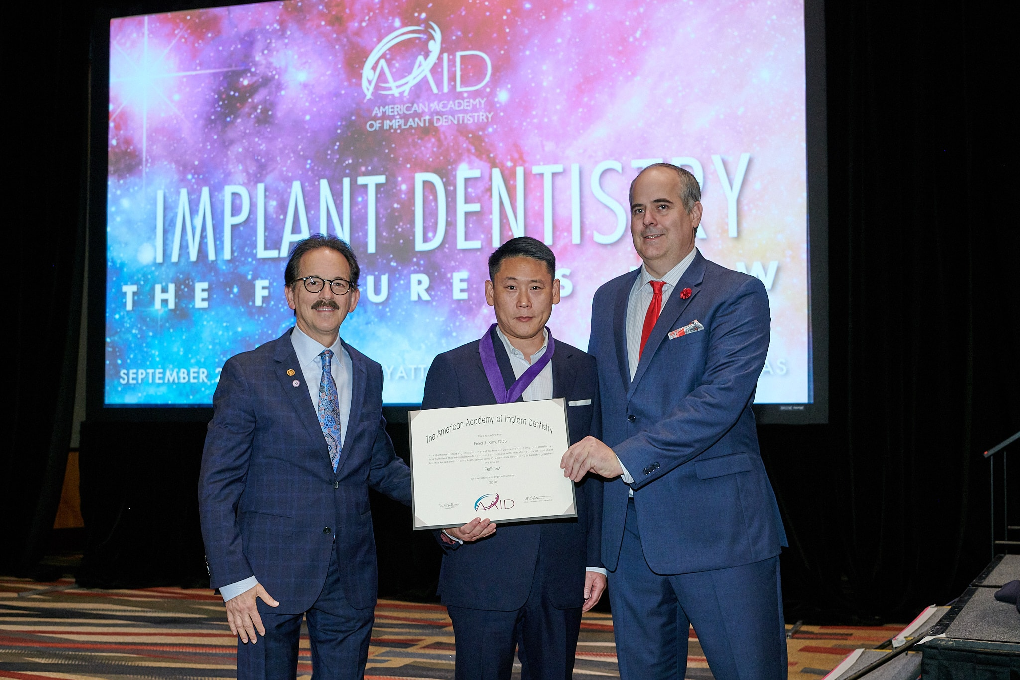 American Academy of Implant Dentistry giving the Fellow Certification to Fred J. Kim, DDS of Pacific Smiles