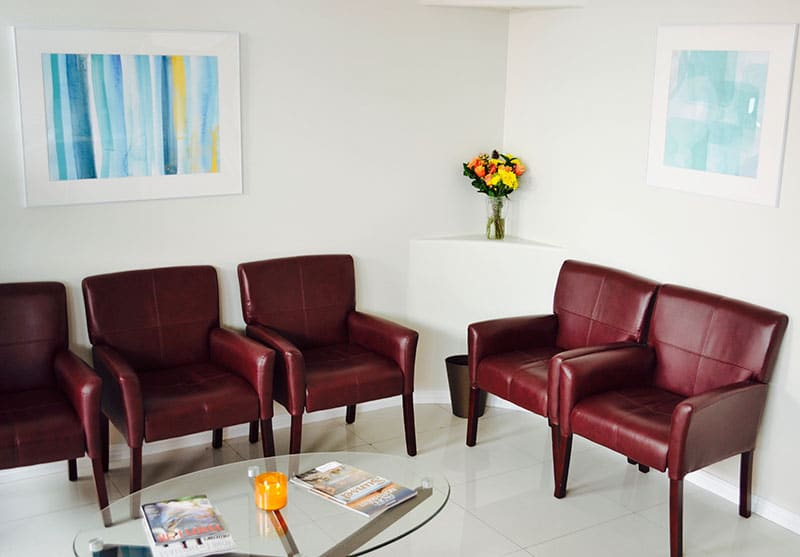 Pacific Smiles front office with chairs, a decorative plant, coffee tables, and an artwork hung on the wall